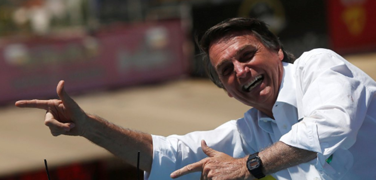 Jair Bolsonaro faz sinal de armas com as mãos