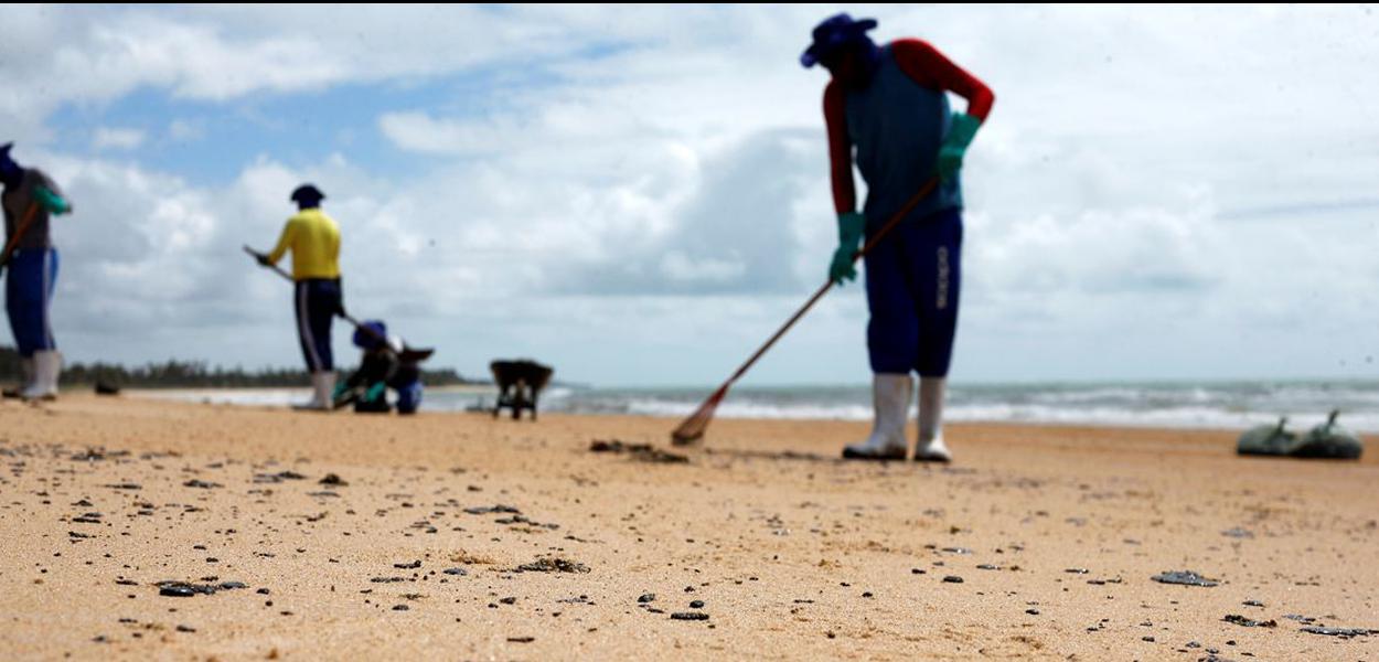 As pessoas removem um derramamento de óleo na praia de Coruripe, estado de Alagoas, Brasil, 14 de outubro de 2019. REUTERS / Adriano Machado