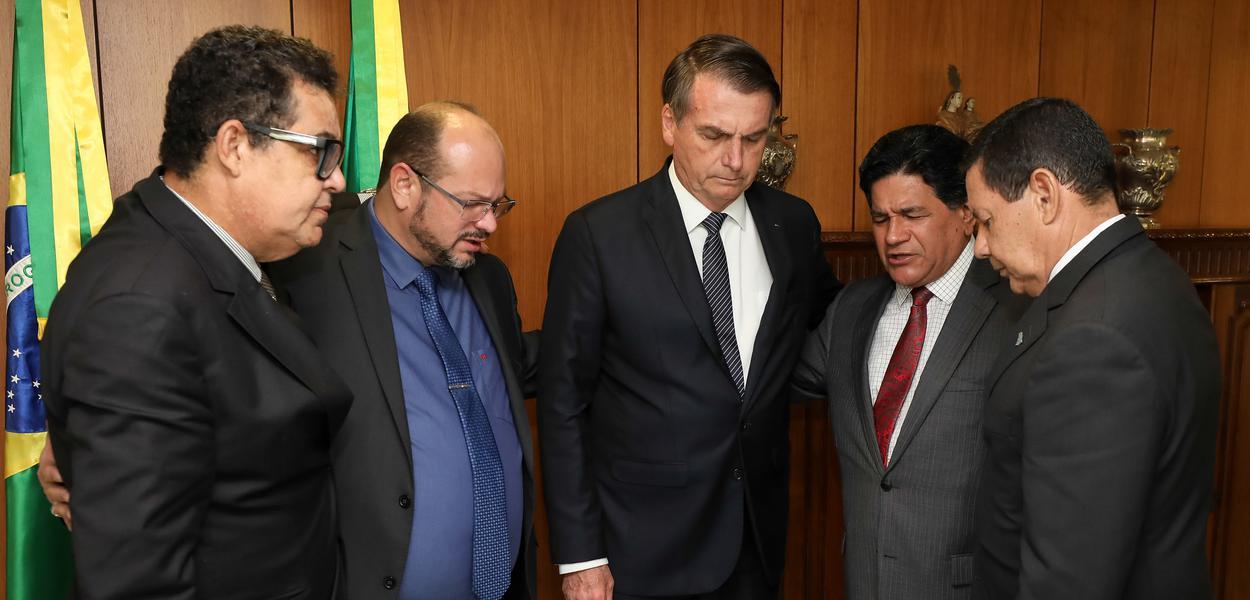 Jair Bolsonaro orando com Mourão e pastores