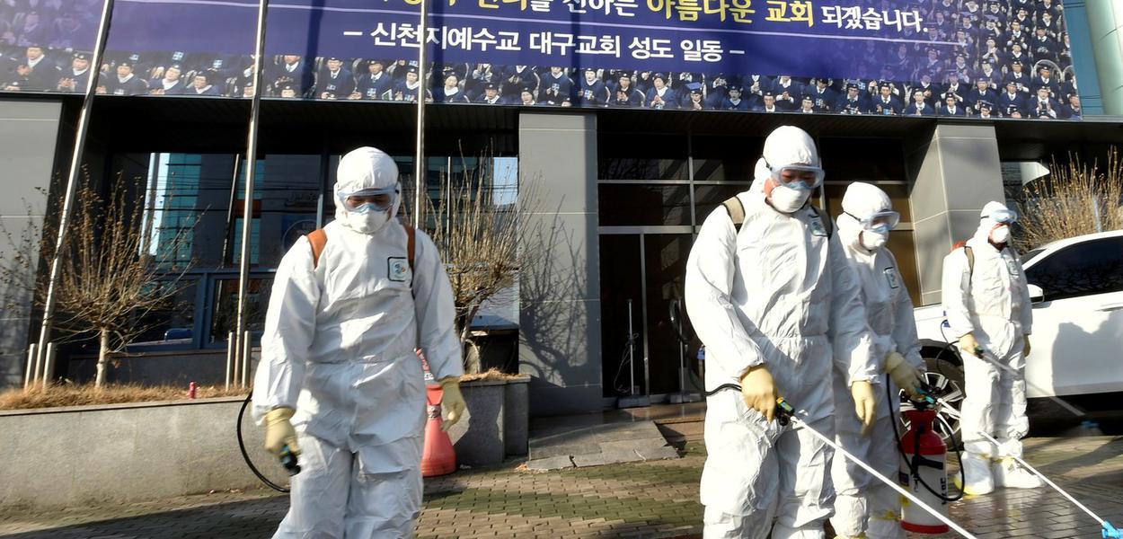 Funcionários de uma empresa de dedetização  desinfectam rua em frente à Igreja de Jesus o Templo do Tabernáculo do Testemunho, em Daegu
