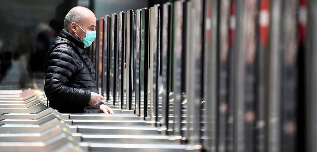 Homem de máscara em estação de metrô de Milão