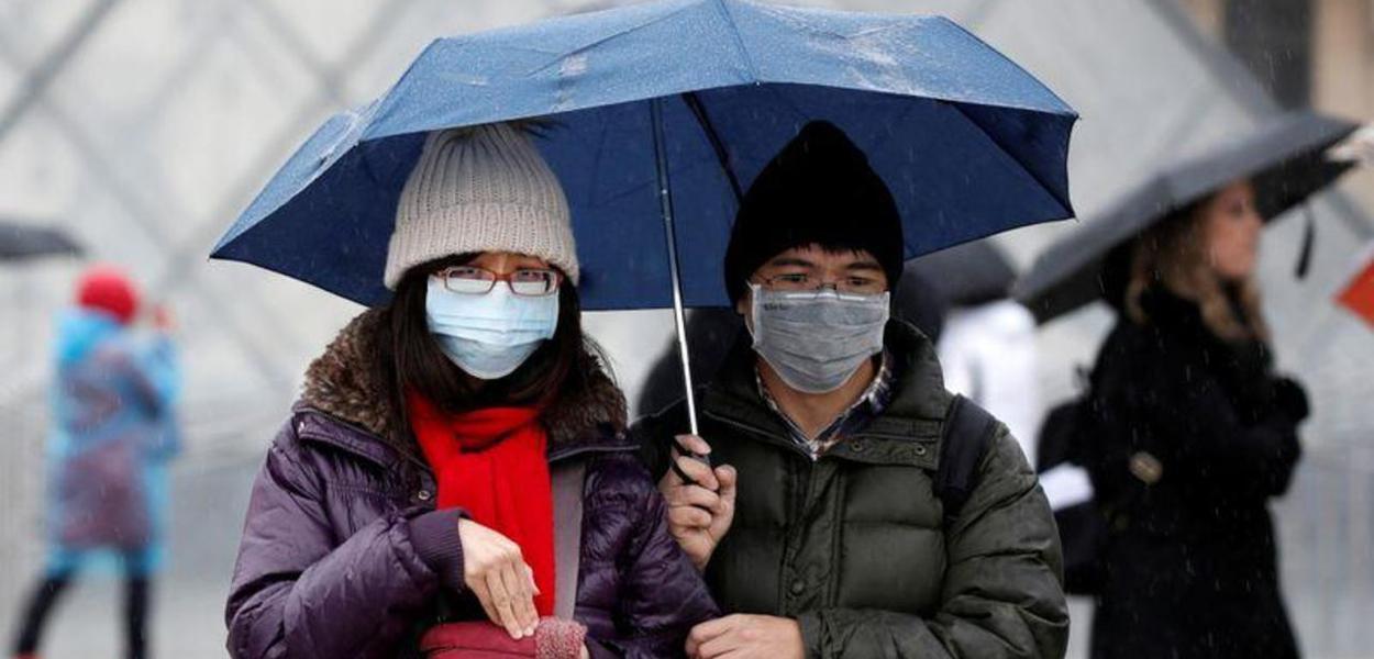 Pessoas de máscara em frente ao Museu do Louvre, em Paris