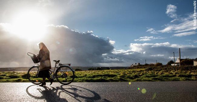 Mulher e bicicleta na ilha de Ouessant, na França