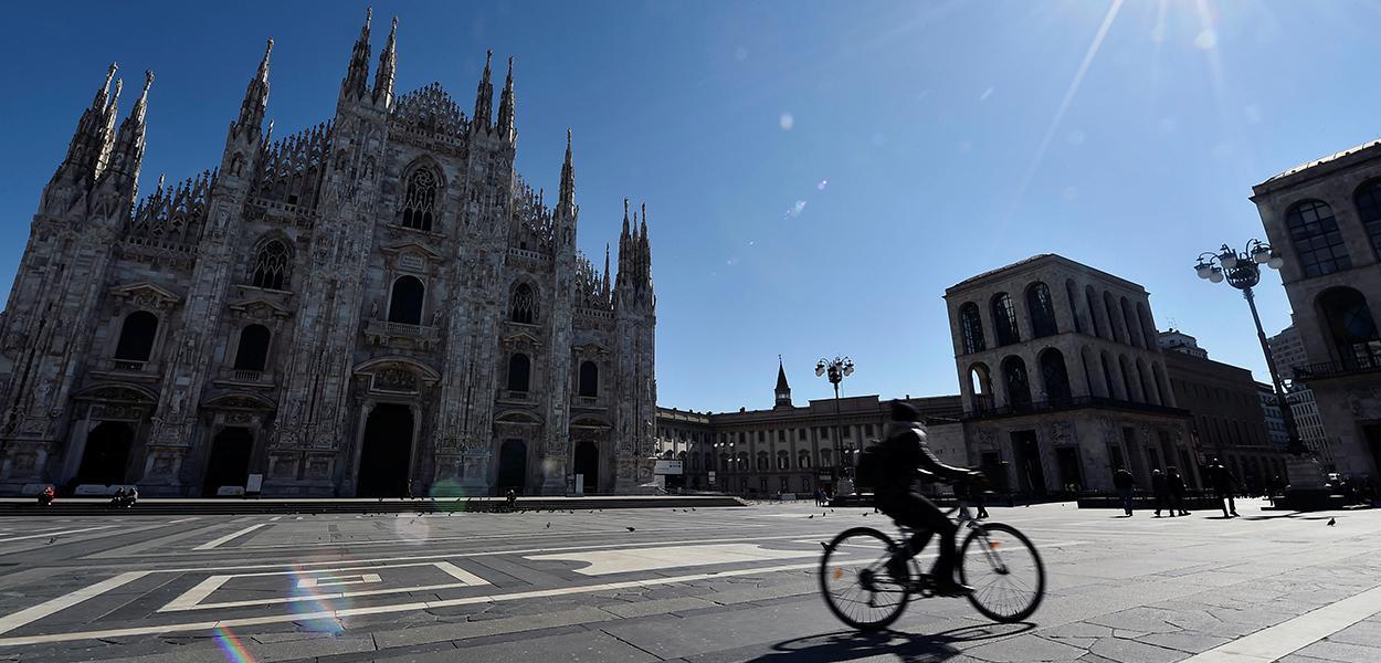 Ciclista passa em frente à catedral de Milão, com ambientes públicos desertos por conta do coronavírus