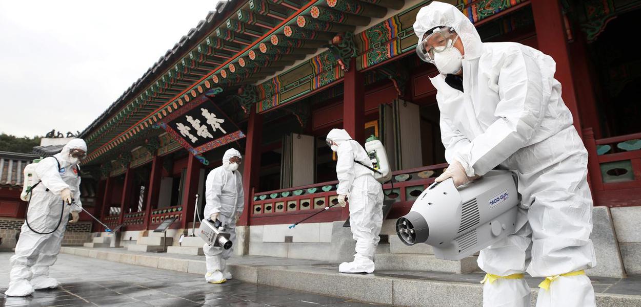 Agentes de saúde sanitizam palácio tradicional de Suwon, na Coreia do Sul, por temor de disseminação do coronavírus da China.