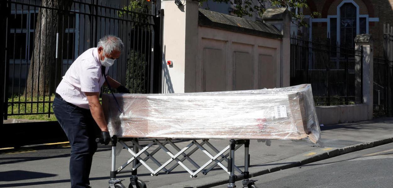 Empregado de uma funerária faz entrega de caixões nesta quarta-feira (25) na casa de repouso da Fundação Rothschild, em Paris, onde 16 pessoas morreram e 81 foram infectadas pelo coronavírus