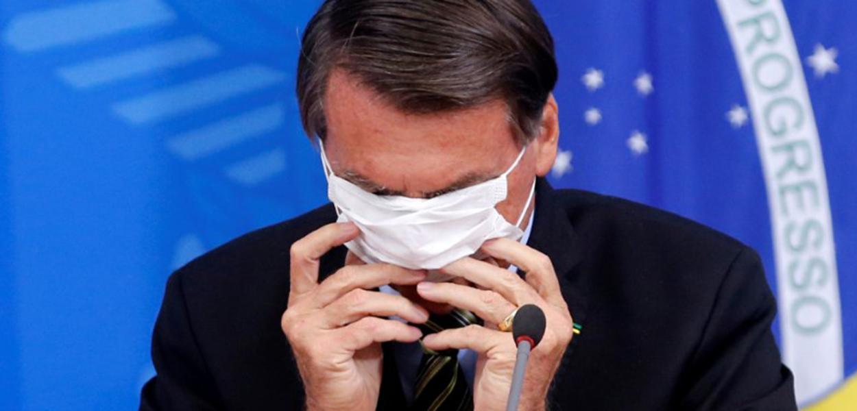 Jair Bolsonaro coloca máscara durante entrevista coletiva sobre coronavírus no Palácio do Planalto