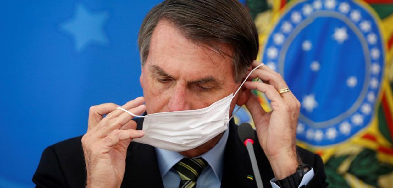 Presidente Jair Bolsonaro ajusta máscara de proteção durante coletiva sobre medidas para evitar a disseminação do coronavírus