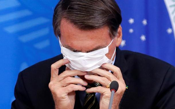 Presidente Jair Bolsonaro coloca máscara durante entrevista coletiva sobre coronavírus no Palácio do Planalto