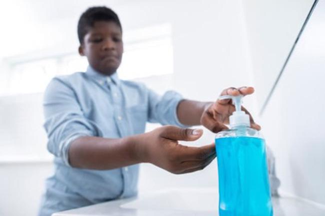 Garoto afro-americano desinfeta as mãos com álcool