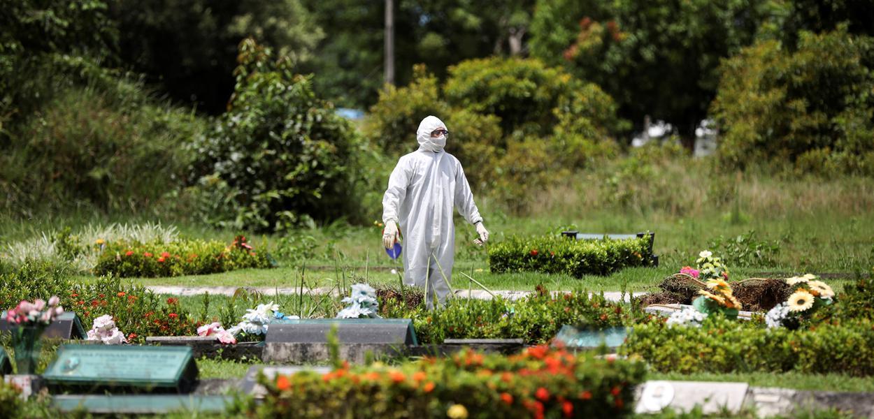 Um coveiro é visto durante o enterro de Ester Melo da Silva, 67 anos, que morreu em razão da doença por coronavírus (COVID-19), no cemitério Parque Tarumã em Manaus, AM, Brasil.