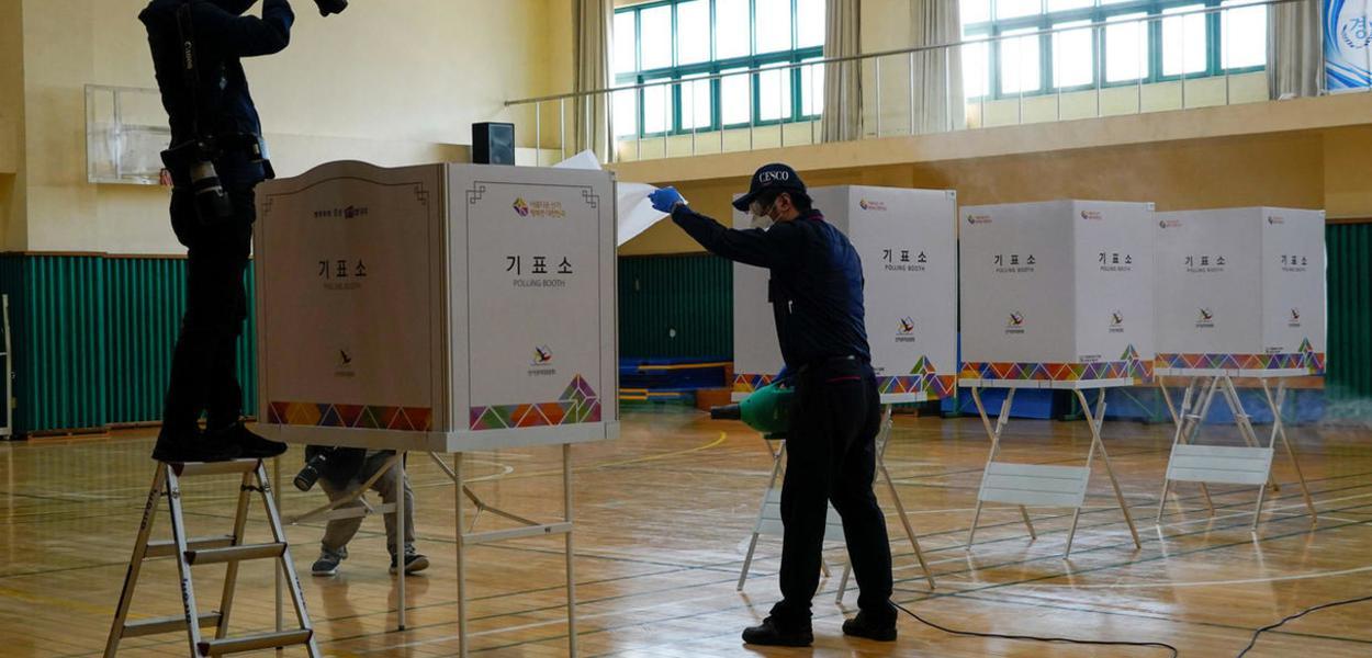 Funcionários de uma empresa de limpeza preparam uma sala que vai servir de seção eleitoral durante as eleições legislativas na Coreia do Sul, na quarta-feira, 15 de abril de 2020