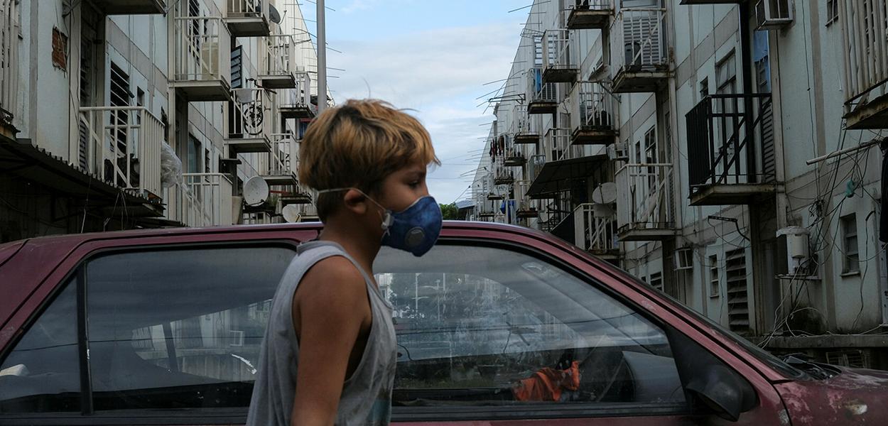 Menino com máscara de proteção na favela de Manguinhos, no Rio de Janeiro