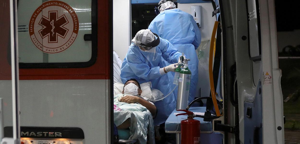 Agentes de saúde transferem paciente do novo coronavírus em ambulância em Manaus