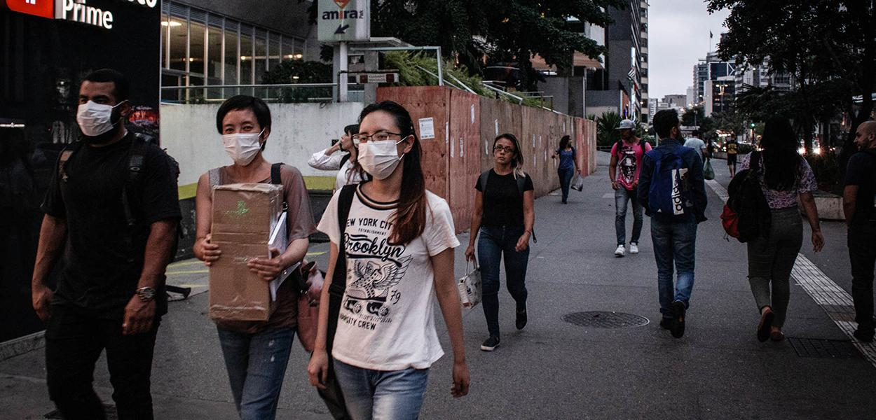 Protegidos com mascaras por causa da pandemia do Coronavírus, paulistanos caminham na avenida Paulista