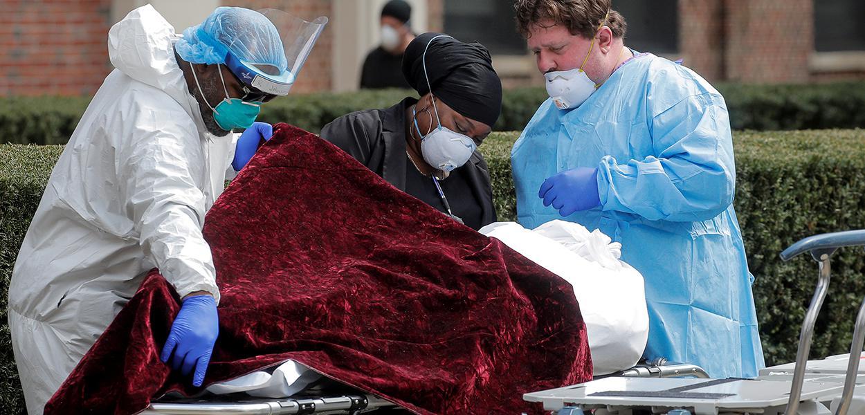 Profissionais de saúde se preparam para transferir o corpo de uma pessoa que morreu no Kingsbrook Jewish Medical Center durante o surto da doença por coronavírus (COVID-19), no bairro de Brooklyn, em Nova York, EUA
