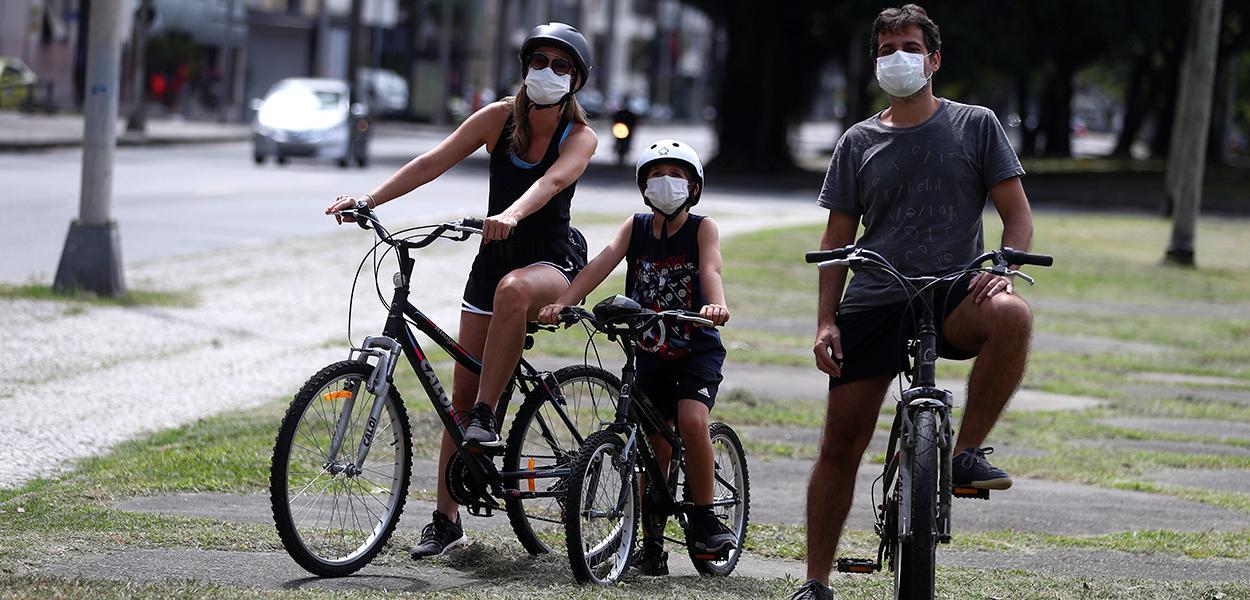 Família com máscara de proteção em praça