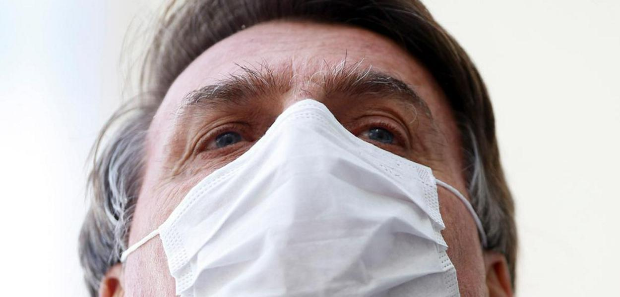 Brazil's President Jair Bolsonaro wearing a protective mask speaks with journalists, amid the coronavirus disease (COVID-19) outbreak, at the Planalto Palace, in Brasilia, Brazil May 12, 2020.