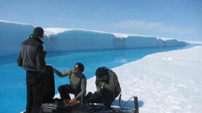 Cientistas na borda de um rio formado por gelo derretido, na Groenlândia
