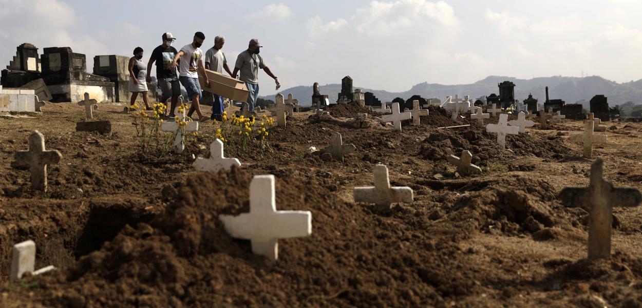 Marcos Vinicius Andrade da Silva, 26, ajuda a carregar no Cemitério de Inhauma o caixão de Valnir Mendes da Silva, 62, que morreu em uma calçada na favela Arará após dificuldades para respirar, em meio à pandemia do novo coronavírus. Rio de Janeiro, Brasil, 18/05/2020.