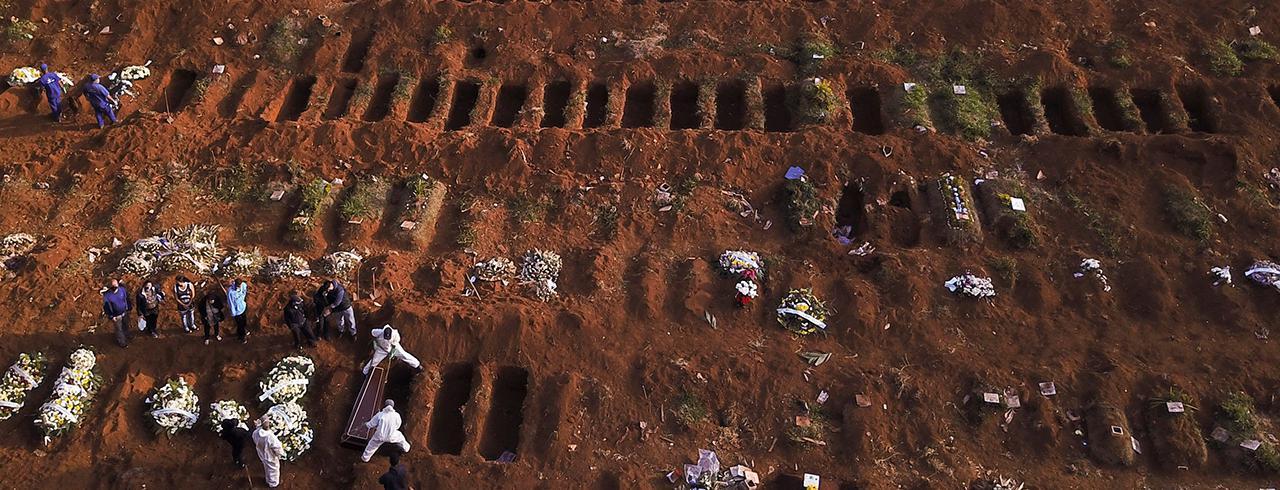 Sepultadores com trajes de proteção enterram vítima de Covid-19 no cemitério de Vila Formosa, em São Paulo 22/05/2020