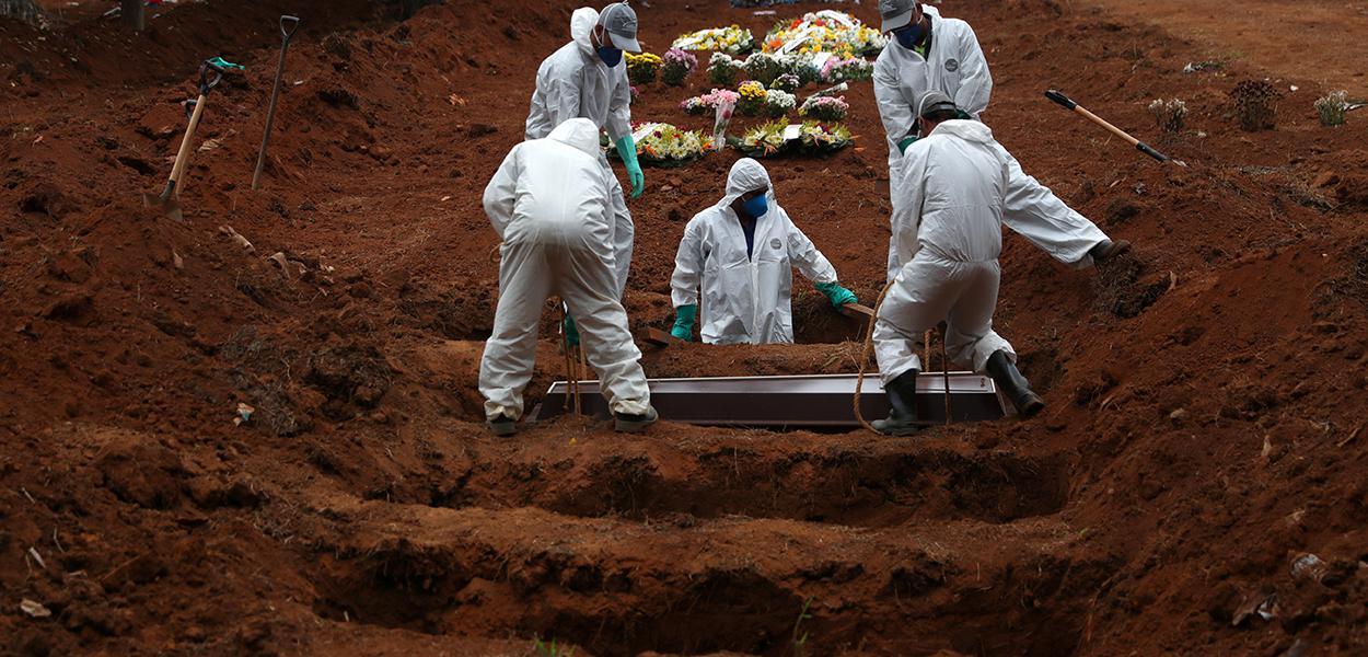 Coveiros com trajes de proteção enterram homem morto pela Covid-19 em cemintério em São Paulo 04/06/2020