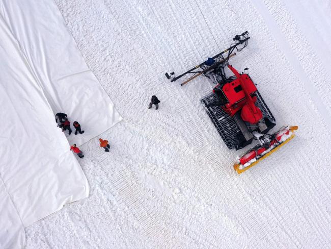 Tratores são usados para espalhar o lençol de plástico