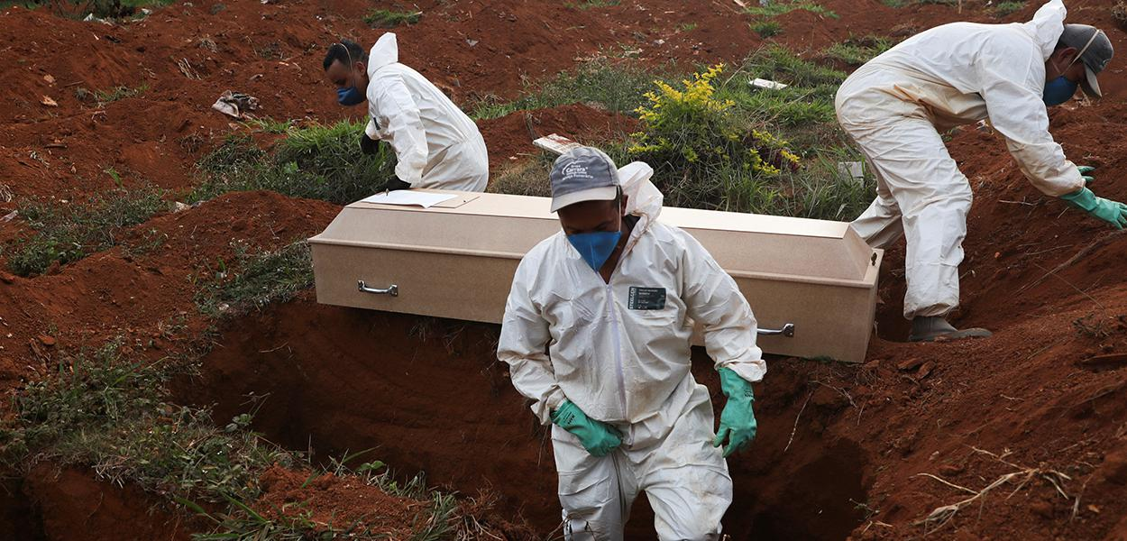 Coveiros com trajes de proteção enterram pessoa que morreu infectatada pelo novo coronavírus