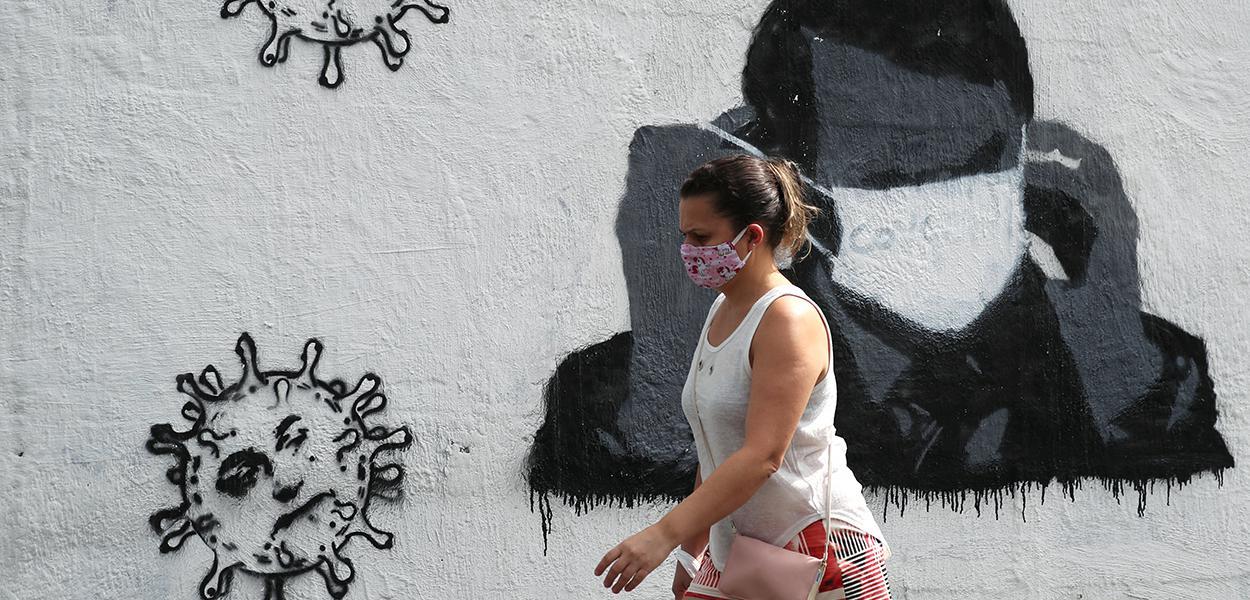 Mulher passa por grafite do presidente Jair Bolsonaro ajustando sua máscara protetora e em forma de vírus, em meio ao surto de Covid-19 no Rio de Janeiro.