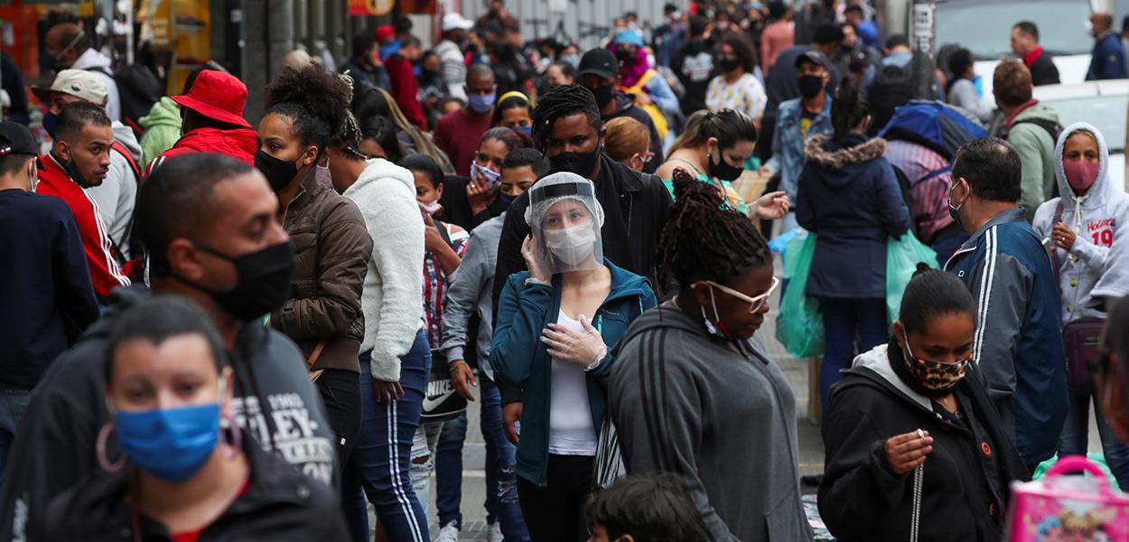 Pessoas com máscaras de proteção facial caminham em rua de comércio popular em São Paulo