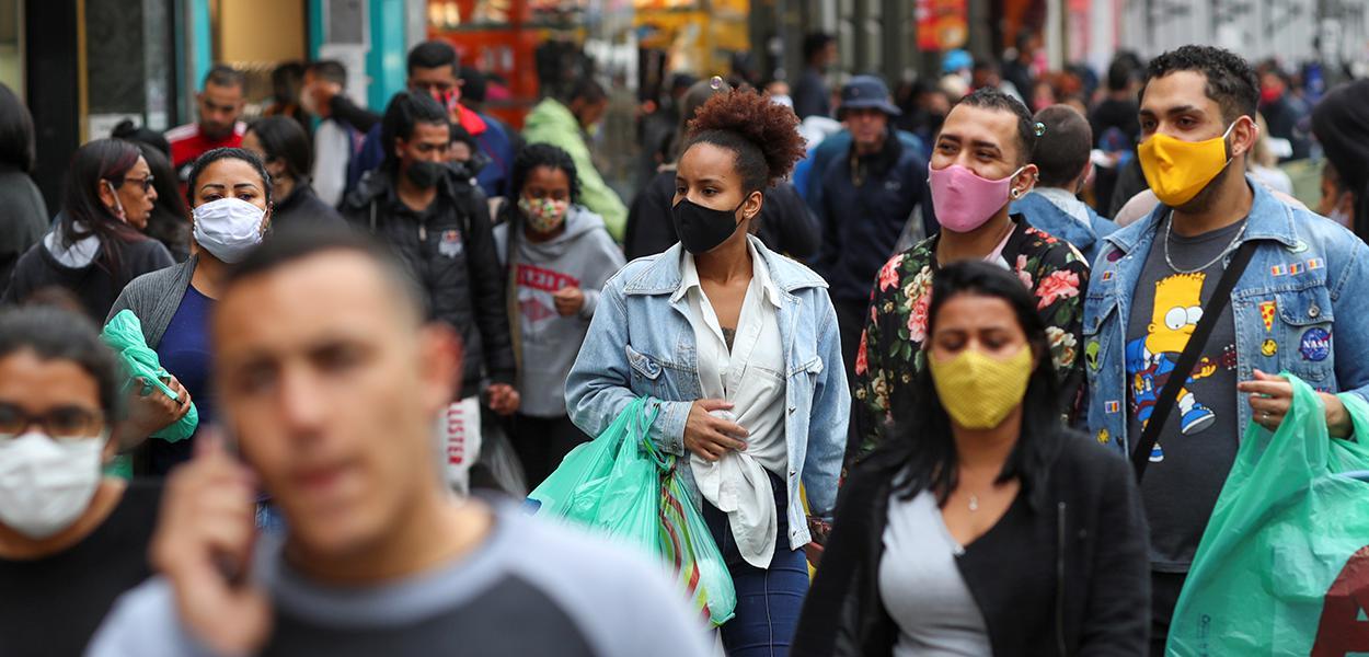 Pessoas com máscaras faciais caminham em rua de comércio popular em São Paulo 15/07/2020
