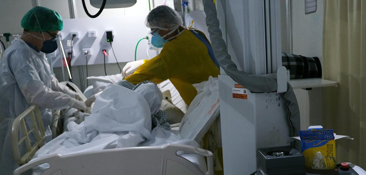 Profissionais da área da saúde examinam paciente com Covid-19.
