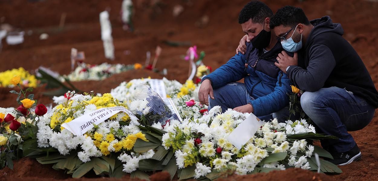 Familiares de mulher que morreu vítima da Covid-19 choram durante enterro em cemitério Vila Formosa, em São Paulo