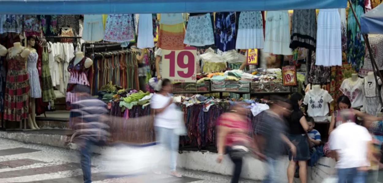 Pessoas passam em frente a loja em rua comercial de São Paulo