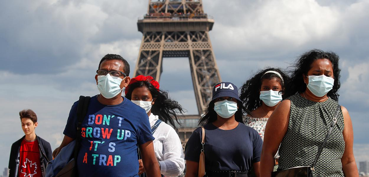 Pessoas com máscaras de proteção perto da Torre Eiffel, em Paris