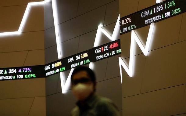 Homem usando máscara de proteção passa próximo de painel com cotações do mercado financeiro. 8/9/2020
