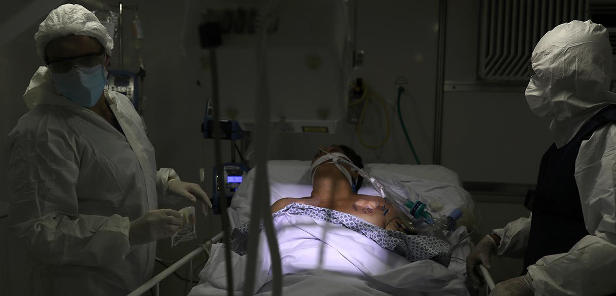 Membros da equipe médica, utilizando roupas de proteção e máscaras faciais, fazem um raio-X de pulmão em um paciente com doença coronavírus (COVID-19) na Unidade de Terapia Intensiva (UTI) de um hospital de campanha criado para tratar pacientes que sofrem de doença (COVID-19) em Guarulhos, São Paulo. 12/05/2020.