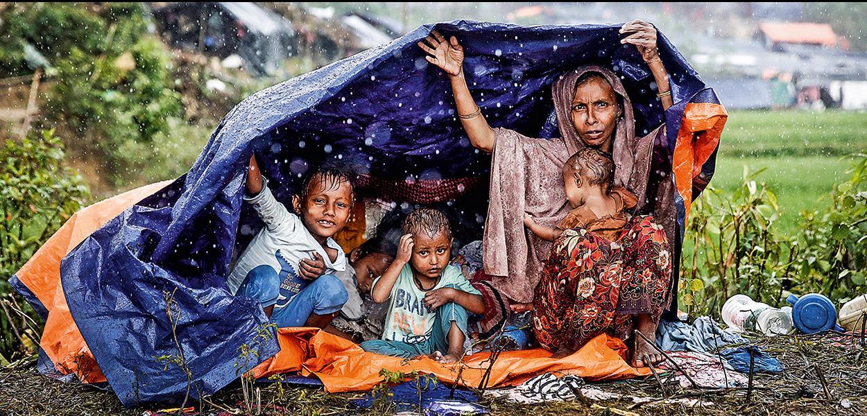 Família rohingya protege-se da chuva em Bangladesh, onde se refugiou: assassinatos e estupros contra muçulmanos de Mianmar - 30/08/2018