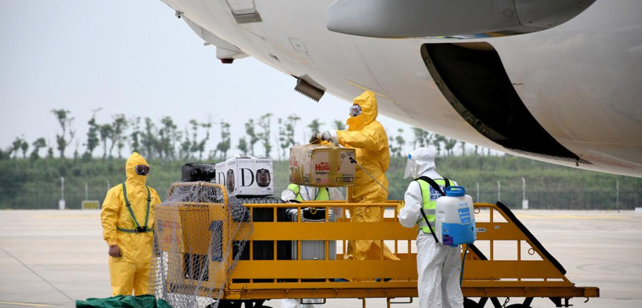Trabalhadores em trajes de proteção desinfetam bagagens que chegam no Aeroporto Internacional de Wuhan