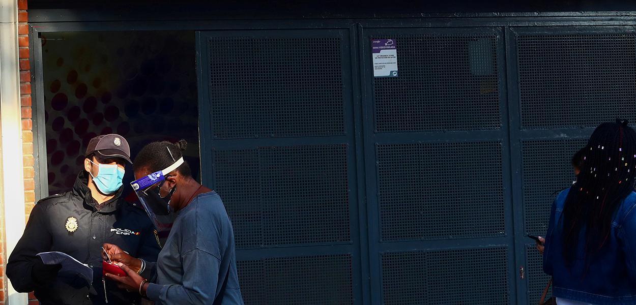 Agente da polícia nacional da Espanha checa documentos de mulher em Madri