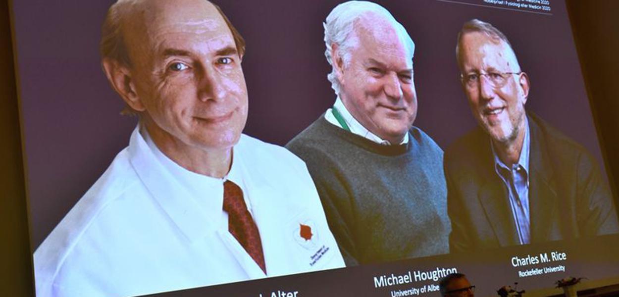 Fotos dos cientistas Harvey J. Alter, Michael Houghton e Charles M. Rice aparecem em tela durante anúncio de vencedores do Prêmio Nobel de Medicina em Estocolmo
