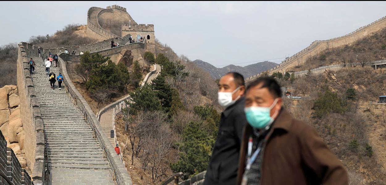 Mesmo de máscara, turistas já são vistos na Muralha da China.