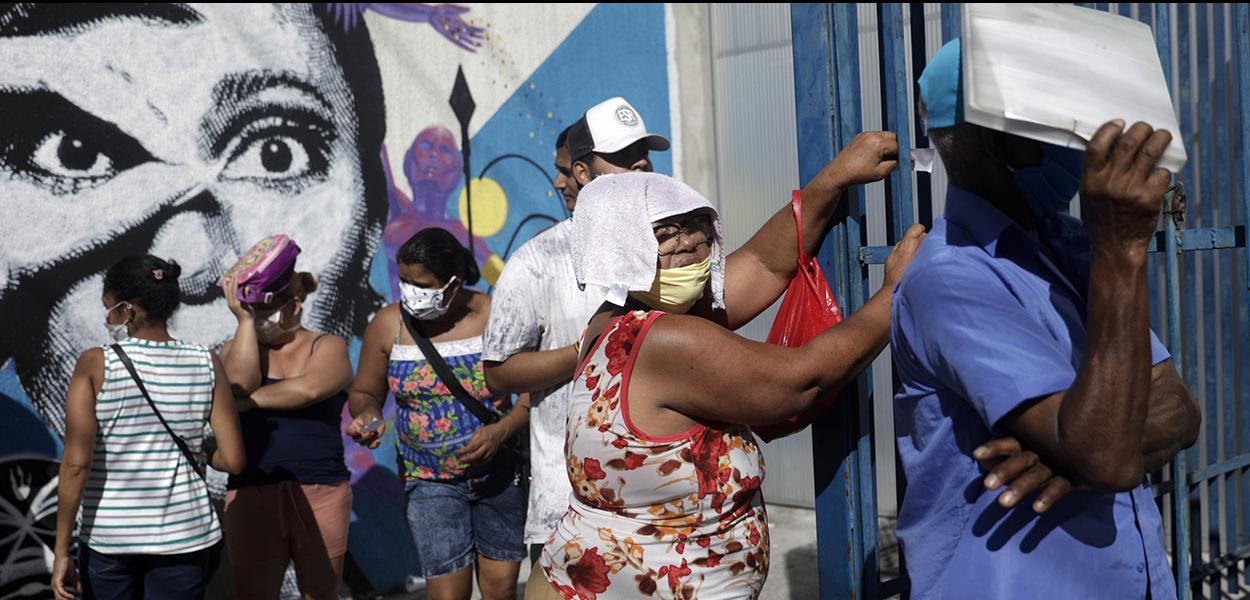 Pessoas esperam em fila do lado de fora de agência da Caixa para receber o auxílio emergencial do governo durante a pandemia. 27/04/2020