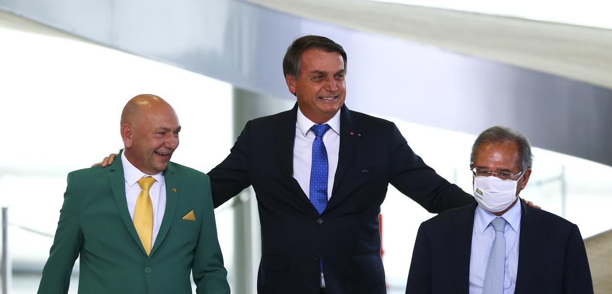 O empresário Luciano Hang, Jair Bolsonaro e o ministro da Economia, Paulo Guedes, durante o lançamento do programa Voo Simples, no Palácio do Planalto.