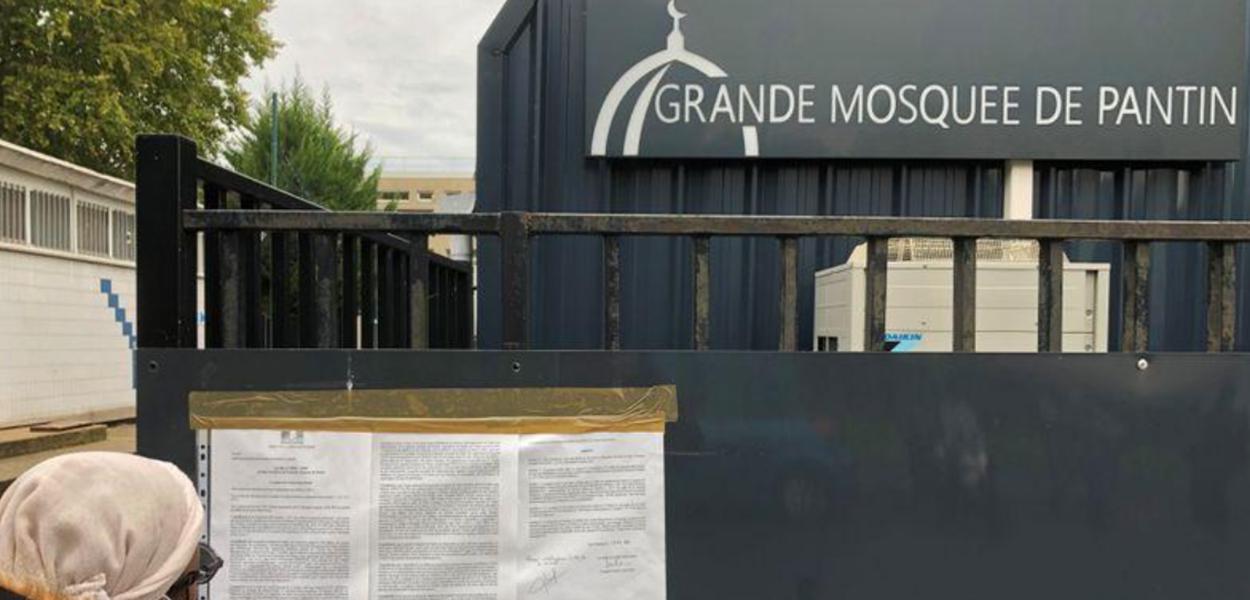 Mulher lê decreto na entrada da Grande Mesquista de Pantin