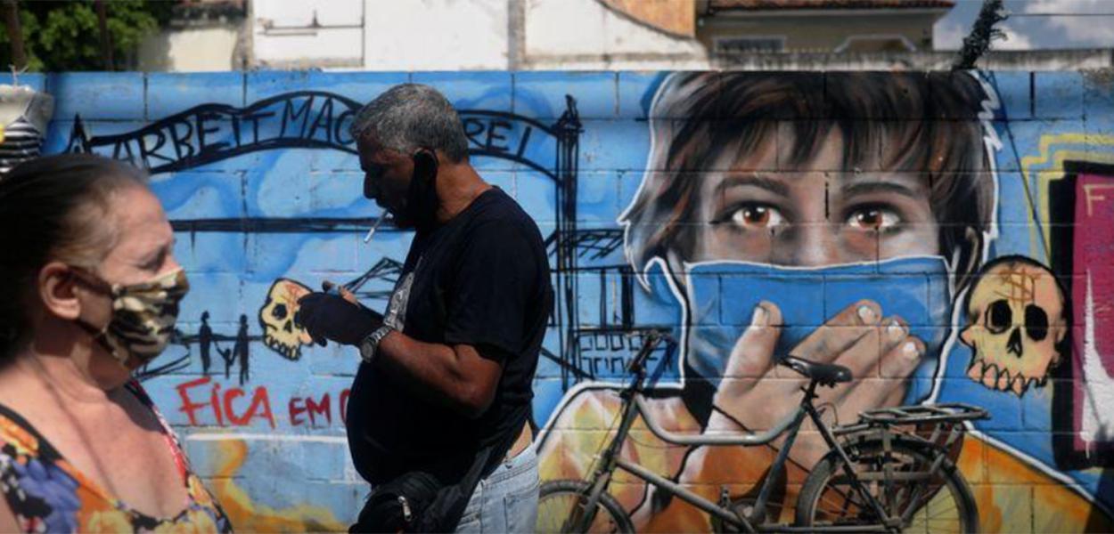 Pessoas usando máscaras de proteção passam em frente a grafite em meio à pandemia da Covid-19 no Rio de Janeiro