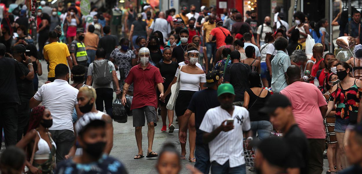 Pessoas caminham por rua de comércio popular no centro de São Paulo