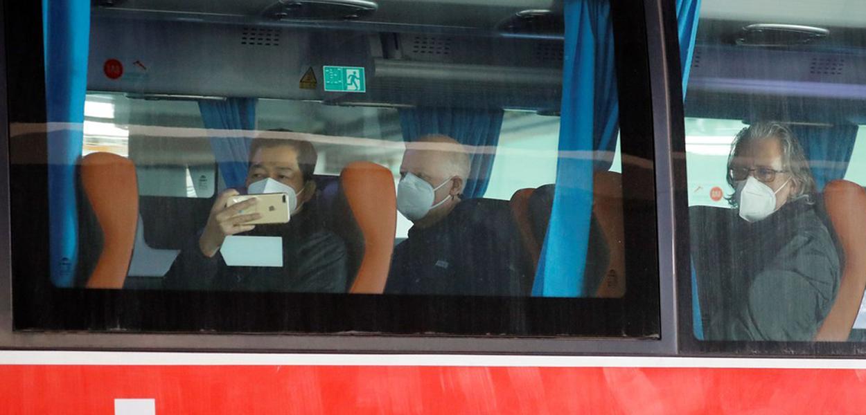 Membros da equipe da Organização Mundial da Saúde (OMS) encarregada de investigar as origens da pandemia do coronavírus sentam em um ônibus antes de deixar aeroporto de Wuhan.