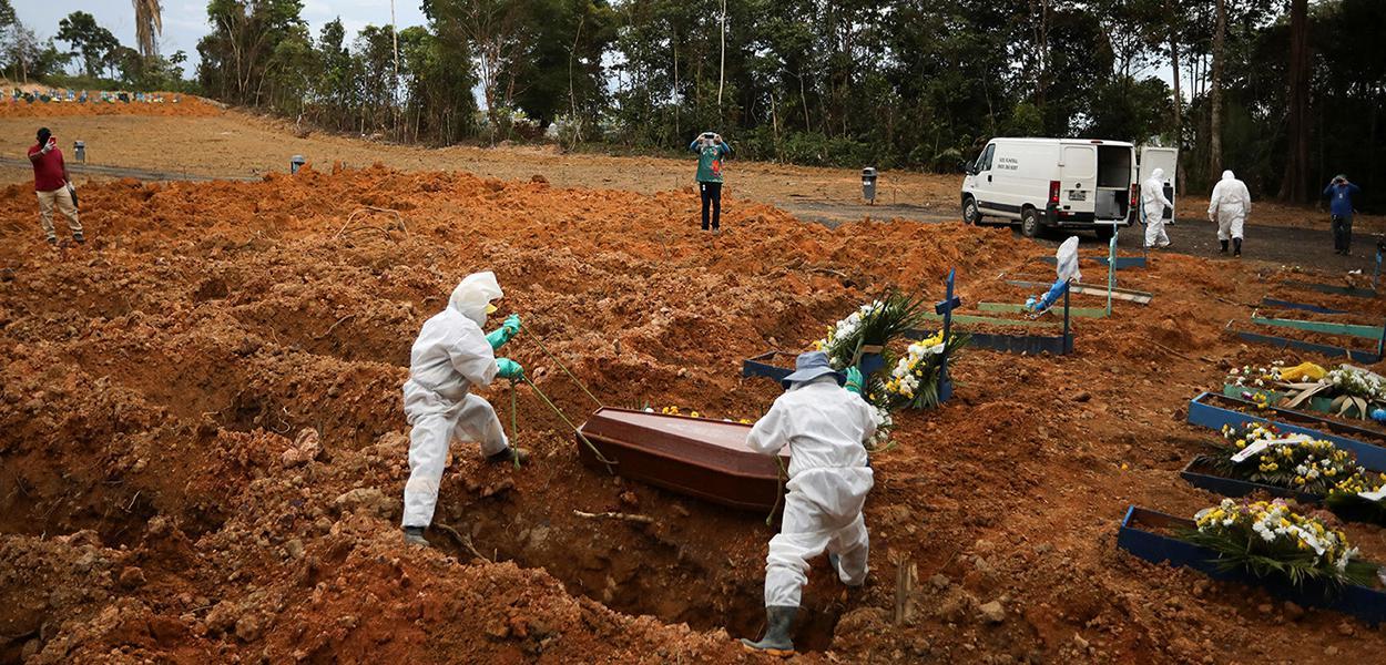 Coveiros vestindo roupas de proteção se preparam para enterrar no cemitério Parque Taruma, em Manaus