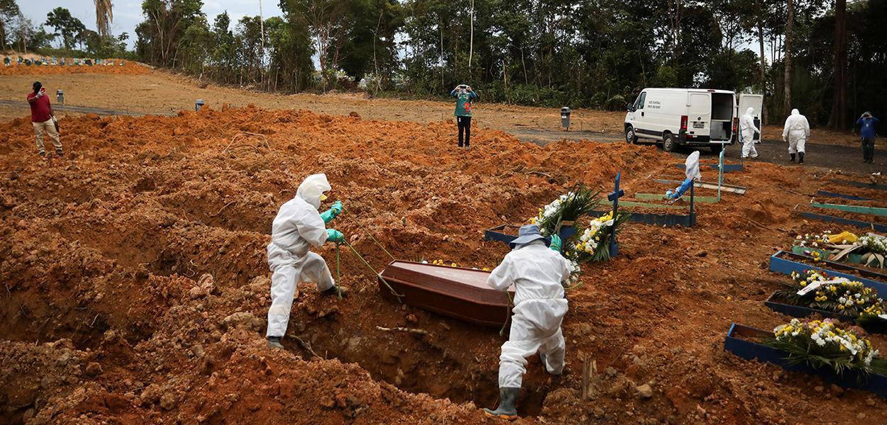 Coveiros vestindo roupas de proteção se preparam para enterrar no cemitério Parque Taruma, em Manaus.